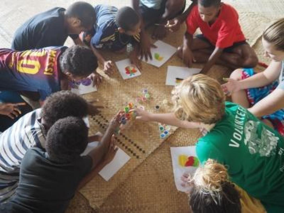 A Projects Abroad volunteer working with children in Fiji sits with a group of children at a special needs school teaching development skills through a painting activity.